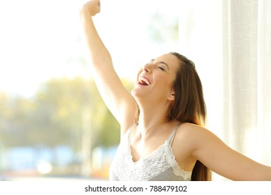 Portrait of an excited girl waking up in a sunny day raising arms beside a window