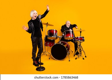 Portrait of excited grey-haired couple performing singing playing live sound isolated over bright vivid shine vibrant yellow color background