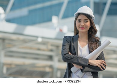 Portrait of excited and happy female architect or engineer holding blueprint and wearing white safety helmet on city background.