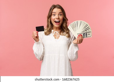 Portrait of excited happy good-looking blond girl in white dress, winning money, placed good bet, made deal, holding dollars money and credit card, smiling amused at camera, pink background