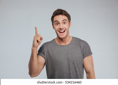 Portrait of an excited happy man pointing finger up at copyspace isolated on a white background
