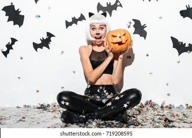 Portrait of an excited happy woman in halloween leather costume posing with carved pumpkin over bats and confetti background