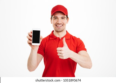 Portrait of a excited happy young delivery man in red cap standing isolated over white background. Looking camera showing display of mobile phone make thumbs up gesture.