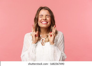 Portrait of excited hopeful blond girl making wish crossed fingers for good luck, close eyes and smiling putting all effort into pray, pleading for dream come true, anticipating over pink background