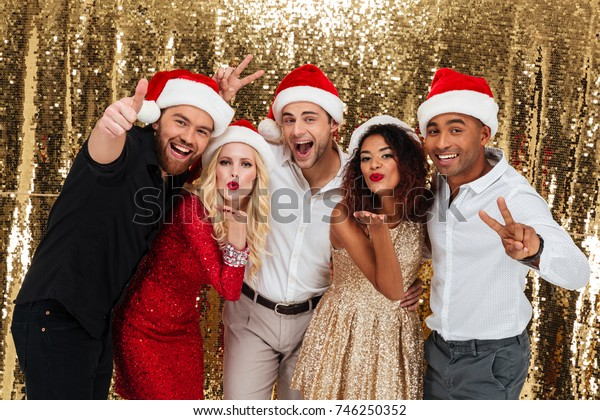 Portrait of a excited joyful multiracial group of friends celebrating New Year together while standing and showing peace gesture isolated over golden shiny background