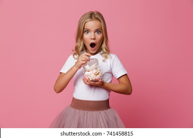 Portrait of an excited little girl holding jar of marshmallow and looking at camera isolated over pink background