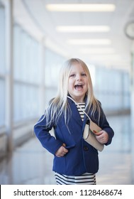 Portrait of excited little girl wearing striped dress and jacket