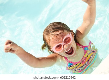 Portrait of excited little girl wearing sunglasses swimming in pool, looking at camera and shouting raising arms