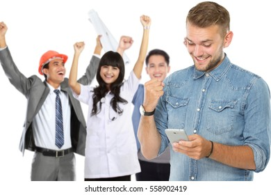 portrait of excited man receiving a text message to his mobile phone. people raised arm at the background