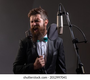 Portrait of excited man in a recording studio. Expressive bearded man in suit with microphone. Karaoke signer, musical vocalist.
