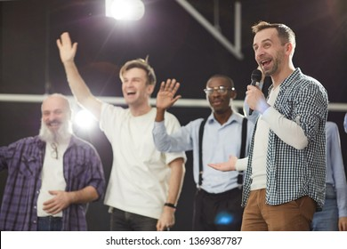 Portrait of excited mature man speaking to microphone on stage with people waving in background, copy space