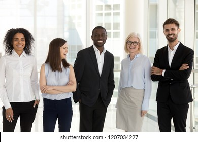 Portrait of excited multiethnic work team standing in modern office posing near big windows, smiling diverse employees look at camera happy with career success, satisfied with company opportunities
