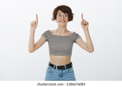 Portrait of excited overwhelmed attractive female studen in round glasses and striped cropped top, raising index fingers and pointing up and smiling joyfully, being impressed and impatient