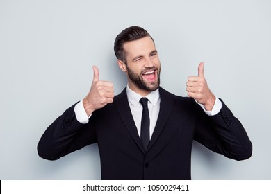 Portrait of excited satisfied cunning cheerful confident curious positive delightful handsome creative active laughing freelancer demonstrating thumbs-up pointing up isolated on gray background shirt
