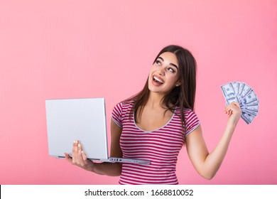 Portrait of an excited satisfied girl holding money banknotes and laptop computer. Happy woman with lucky money. Photo of beautiful woman with laptop, isolated on pink background