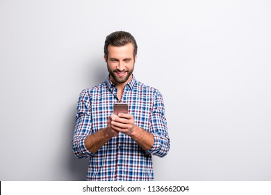 Portrait of excited satisfied with toothy beaming shiny smile having rest relax break pause using smartphone for getting sending sms isolated on gray background copy-sapce