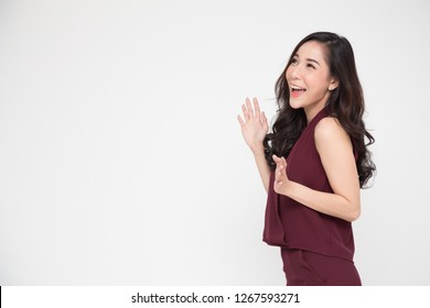 Portrait of excited screaming young asian woman standing in red dress isolated over white background, Wow and surprised business woman concept