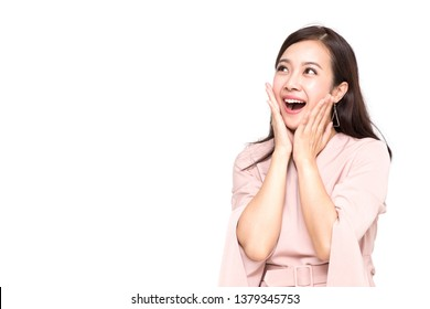 Portrait of excited screaming young asian woman standing in pink dress isolated over white background, Wow and surprised concept