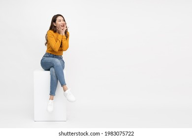 Portrait of excited screaming young asian woman sitting on white box isolated over white background, Wow and surprised concept - Shutterstock ID 1983075722
