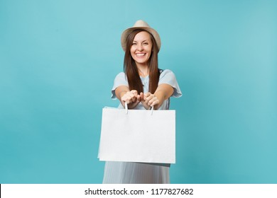Portrait excited smiling beautiful caucasian woman in summer dress, straw hat holding packages bags with purchases after shopping isolated on blue pastel background. Copy space for advertisement