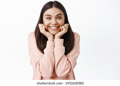 Portrait of excited smiling girl leaning on face and looking enthusiastic at camera, gazing at something with interest and excitement, standing against white background