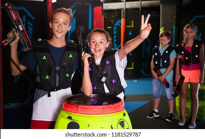 Portrait of excited teen boy and girl with laser guns during lasertag game in dark room