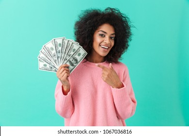 Portrait of excited woman 20s with afro hairstyle pointing finger on fan of money dollar bills isolated over blue background