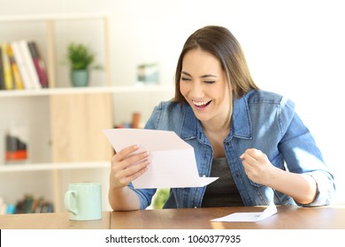 Portrait of an excited woman reading good news in a letter at home