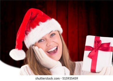 3d878e014495b Portrait of excited woman in santa hat holding a christmas gift during  christmas time