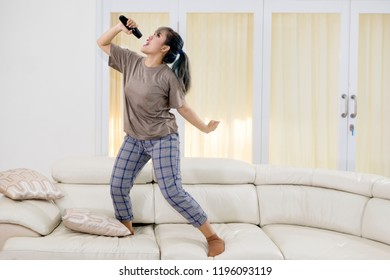 Portrait of an excited woman singing with a remote control while standing on the couch. Shot at home