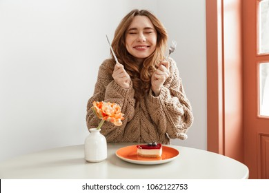 Portrait of an excited woman in sweater getting ready to eat cheesecake on a plate at the table