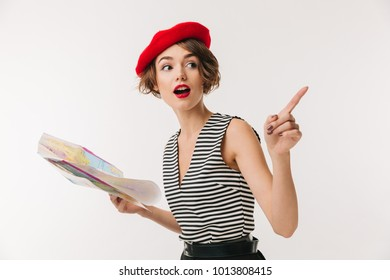 Portrait of an excited woman wearing red beret holding travel map guide and pointing finger away isolated over white background