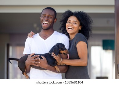 Portrait of excited young African American couple posing with domestic pet outside new family house, happy black husband and wife with cute dog laugh glad to buy first home together. Ownership concept