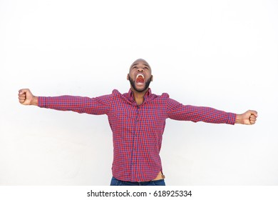 Portrait of excited young african man with arms outstretched shouting against by white wall