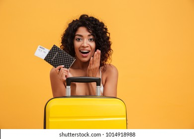 Portrait of an excited young african woman dressed in summer clothes holding passport with flying tickets while standing with a suitcase isolated over yellow background