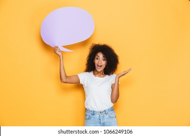 Portrait of an excited young african woman holding empty speech bubble isolated over yellow background
