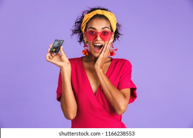 Portrait of an excited young african woman in headband standing over violet background, showing plastic credit card