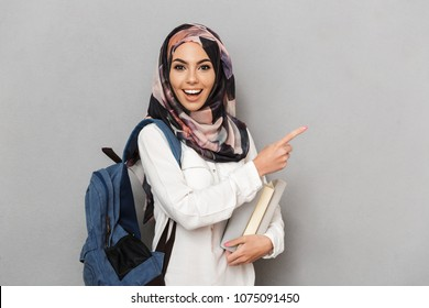 Portrait of an excited young arabian woman student with backpack holding books and pointing finger up isolated over gray background