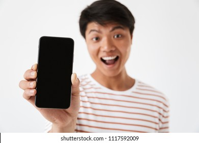 Portrait of an excited young asian man showing blank screen mobile phone isolated over white