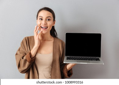 Portrait of an excited young asian woman showing blank screen laptop computer while standing and looking at camera over gray background