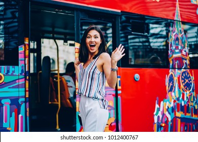 Portrait of excited young asian woman getting in sightseeing bus enjoying visiting city landmarks, surprised female traveler happy about having excursion and city tour in Moscow looking at camera