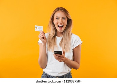 Portrait of an excited young blonde girl showing plastic credit card while holding mobile phone isolated over yellow background