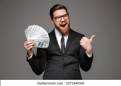 Portrait of an excited young businessman dressed in suit showing money banknotes and giving thumbs up isolated over gray background