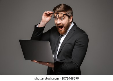 Portrait of an excited young businessman dressed in suit looking at laptop computer isolated over gray background
