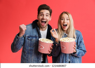 Portrait of an excited young couple dressed in denim jackets standing together isolated over red background, watching movie, eating popcorn