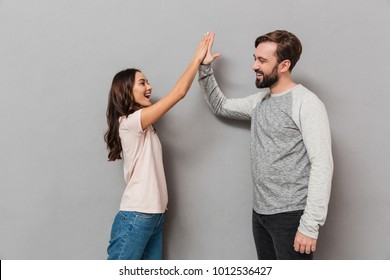 Portrait of an excited young couple giving high five over gray background
