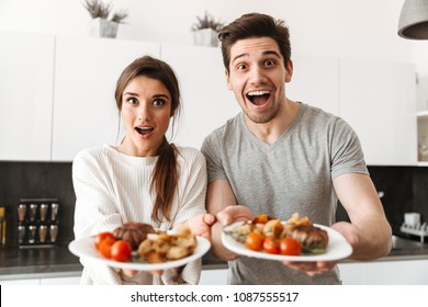 Portrait of an excited young couple holding dinner plates with food while standing at the kitchen