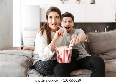 Portrait of an excited young couple relaxing on a couch at home while watching TV and eating popcorn