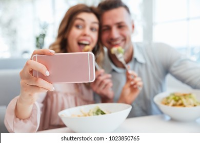 Portrait of an excited young couple taking a selfie while having lunch together at the cafe table indoors