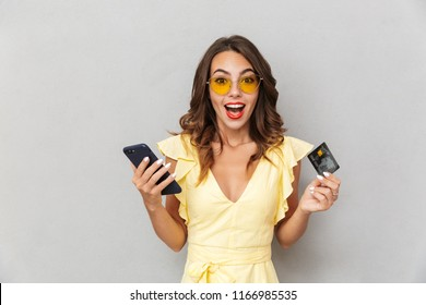 Portrait of an excited young girl in dress standing over gray background, holding mobile phone and showing plastic credit card